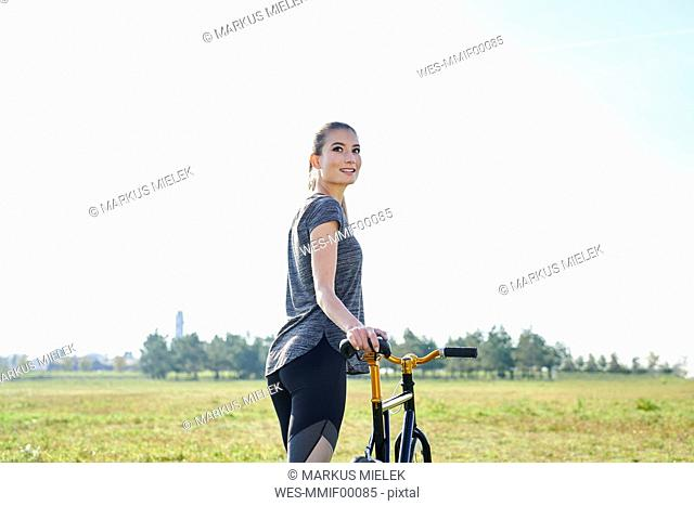 Smiling sportive young woman with bicycle on a meadow