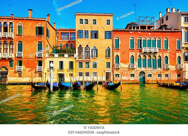 Venice, Italy. Gondolas with floating at piers by Grand Canal among antique buildings and traditional italian Venetian architecture