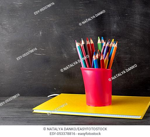 notebook, black stationery glass with multi-colored wooden pencils on the background of an empty black chalk board, back to school concept