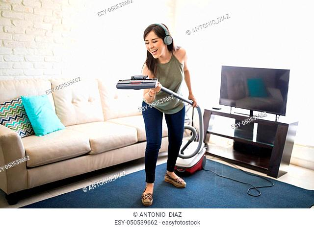 Ecstatic young housewife singing with vacuum cleaner and headphones in living room