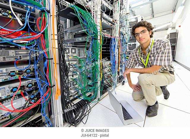 Technician, kneeling and looking at camera, working on laptop computer in Server room of data center