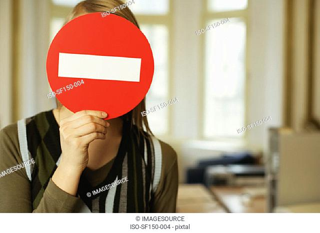 Woman covering her face with a no entry sign