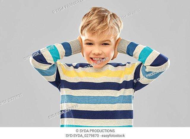 stressed boy in pullover closing ears by hands