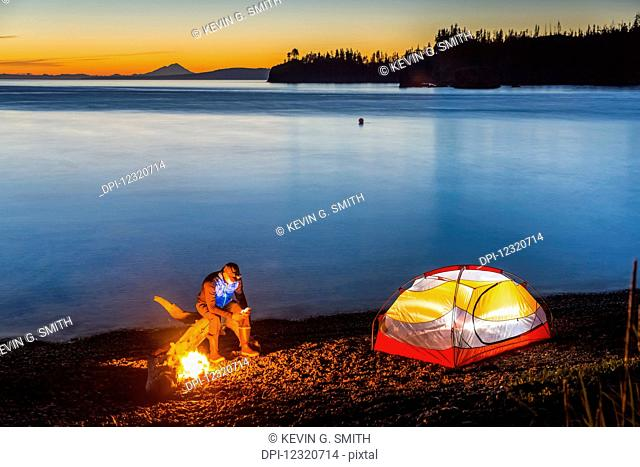 A campfire on a beach at sunset illuminates a nearby tent, with a man sitting near the fire looking at a cell phone with the tranquil ocean water reflecting the...