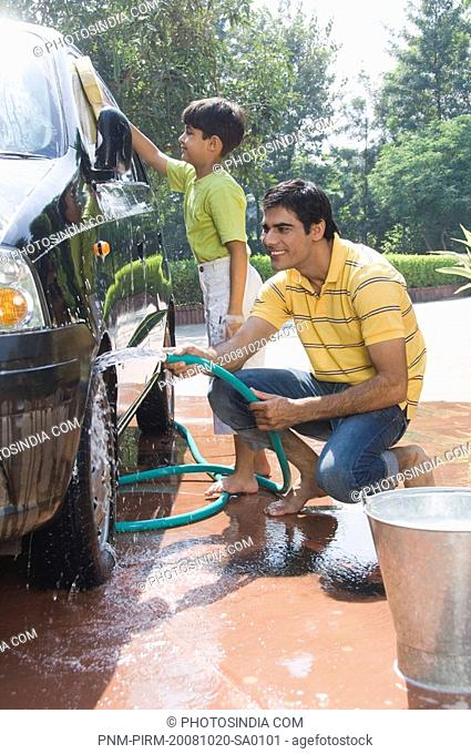 Boy helping his father washing a car and smiling, New Delhi, India