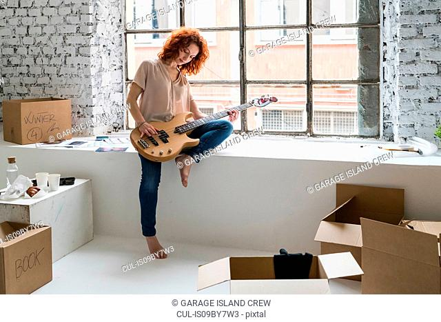Mid adult woman moving into industrial style apartment, sitting on window ledge playing guitar