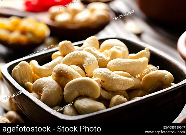 Cashew nuts in clay bowl on kitchen wooden table food background