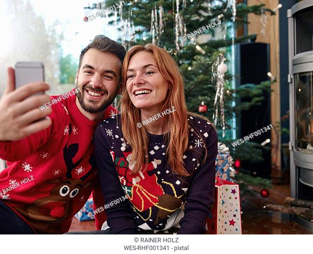 Happy couple taking selfie in front of Christmas tree