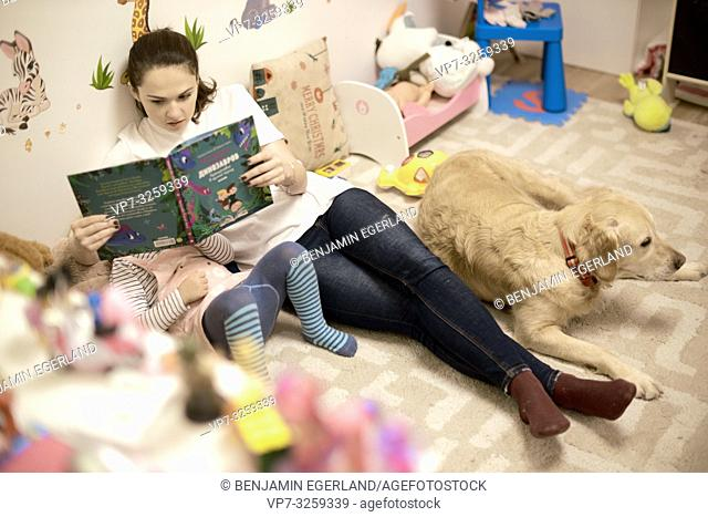 woman reading book with toddler and dog at home in child's room, in Munich, Germany