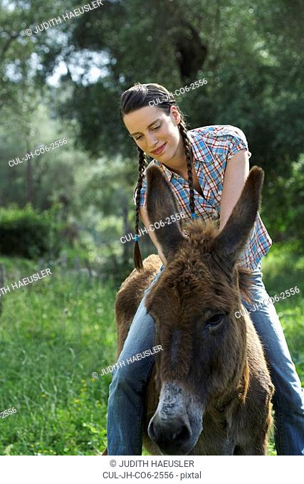 Young girl sitting on donkey happy