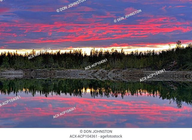 Evening clouds reflected in a pond, near Enterprise, Northwest Territories, Canada