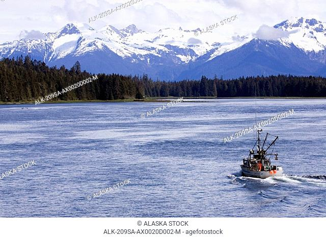 Fishing boat in Wrangell Narrows with Coast Range in background near Petersburg Alaska Inside Passage Southeast summer
