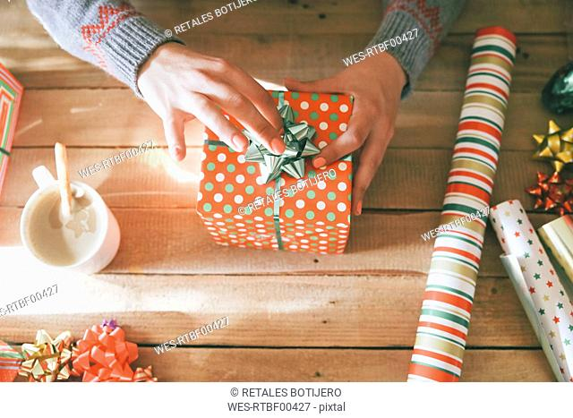 Woman's hands placing tie on Christmas gift