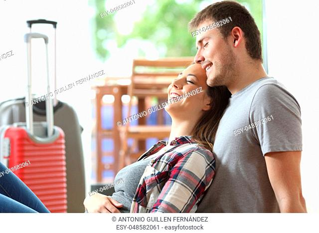 Side view of a romantic couple of tourists resting sitting on the floor of an hotel room