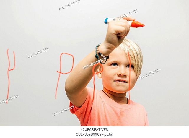 Boy writing reversed letter P onto glass wall