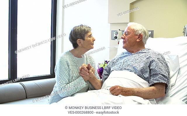 Consultant with digital tablet visiting senior couple in hospital room and gives them good news.Shot on Sony FS700 in PAL format at a frame rate of 25fps