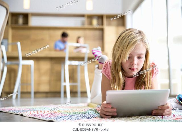 Girl lying on rug browsing digital tablet in living room