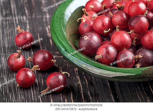Closeup of red gooseberry in bowl. Berries on a wooden table. Blurred background