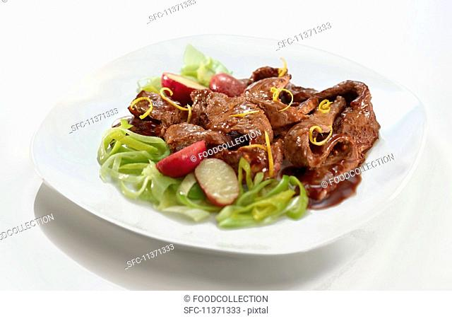 Beef with orange zest on a leek medley with radishes