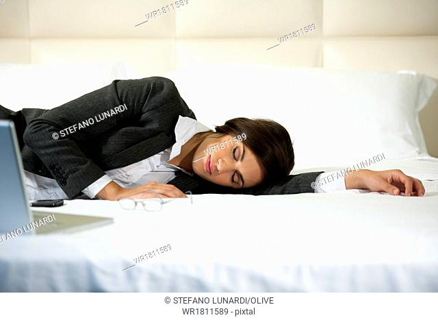 Businesswoman asleep on the bed, hotel or domestic room