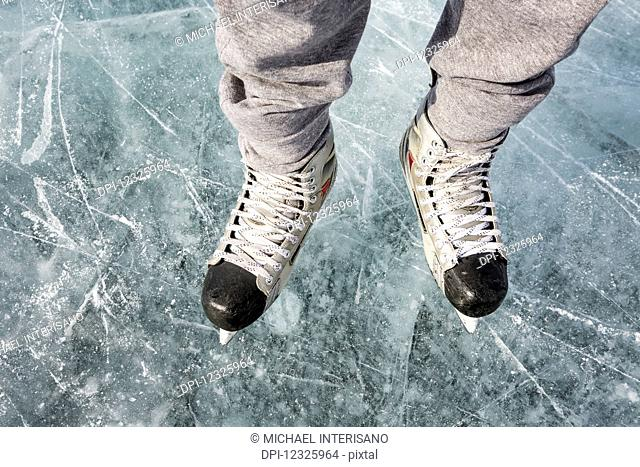 High angle view and close-up of hockey skates on ice; Calgary, Alberta, Canada