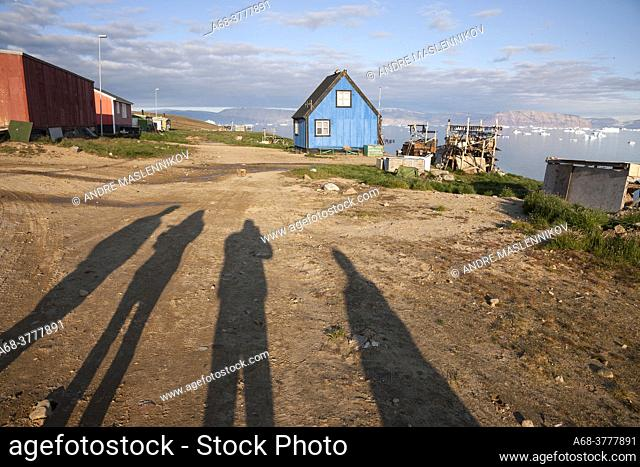 Residential building in Qaanaaq, Greenland. View of the fjord with floating icebergs in the middle of summer