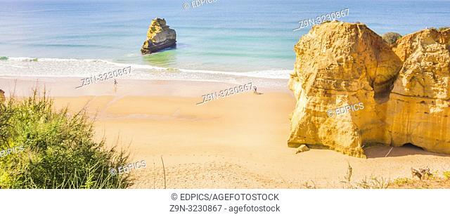 tourists on empty algarve beach in early season, praia da rocha, portimao, algarve, portugal