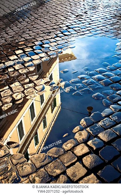 Reflection of house in rain puddle on cobbled street in Trastevere, Rome, Italy