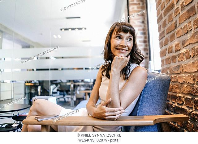 Businesswoman sitting on couch in office, smiling