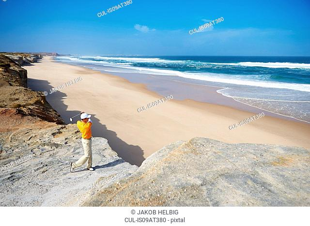 Golfer standing on cliff overlooking beach taking golf swing