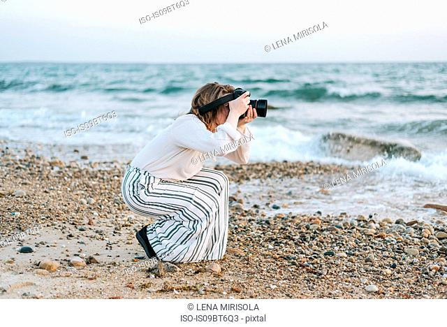 Young woman taking photographs from beach, Menemsha, Martha's Vineyard, Massachusetts, USA