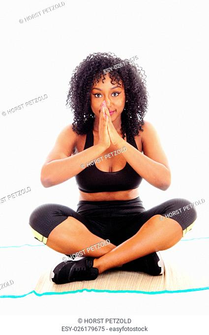 A beautiful African American woman sitting on the floor with her hands.folded and praying, isolated for white background.