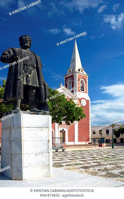 The majestic statue of a portuguese emperor in front of the red colored Chapel de Sao Paolo on the Ilha de Mocambique with blue sky(Island of Mozambique)