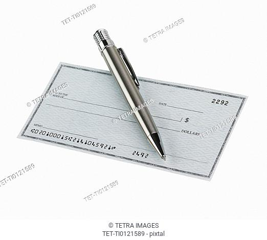 Studio shot of blank check and pen