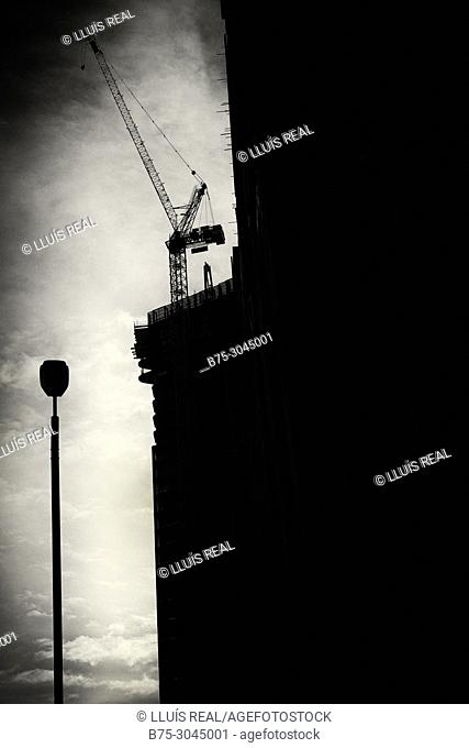 Silhouette of a building in rehabilitation with crane and lamppost, clouds in the sky. Lots Rd. Chelsea, London, England