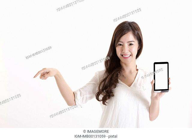 Young business woman holding mobile phone and pointing with smile
