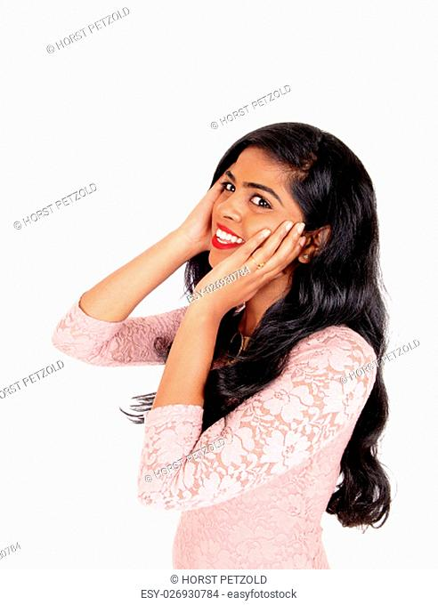 A beautiful smiling Indian woman with long black hair holding her face in.her hand, isolated for white background.