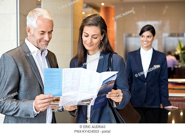Business couple reading a brochure in front of a hotel reception counter