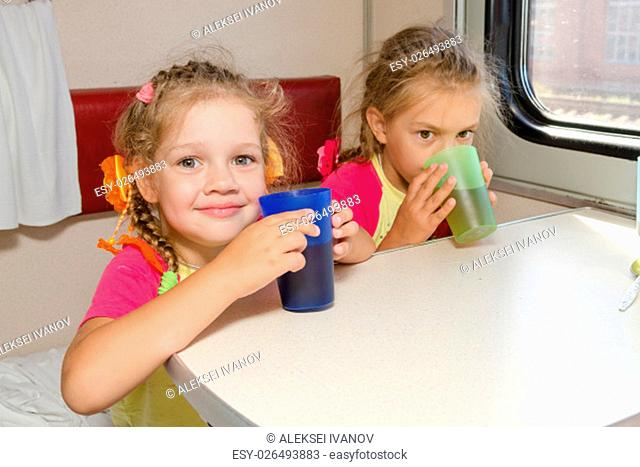 Two little sisters in a train drinking tea at a table on the lower place in the second-class compartment wagon