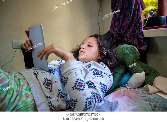 Teenage girl in bed on iPad