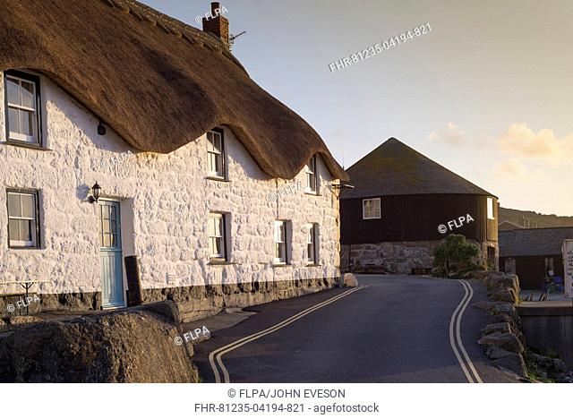 Old fisherman's cottage and The Roundhouse (old capstan house) in coastal village at sunset, Sennen Cove, Sennen, Cornwall, England, May