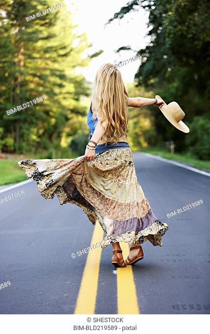 Teenage girl spinning on empty road