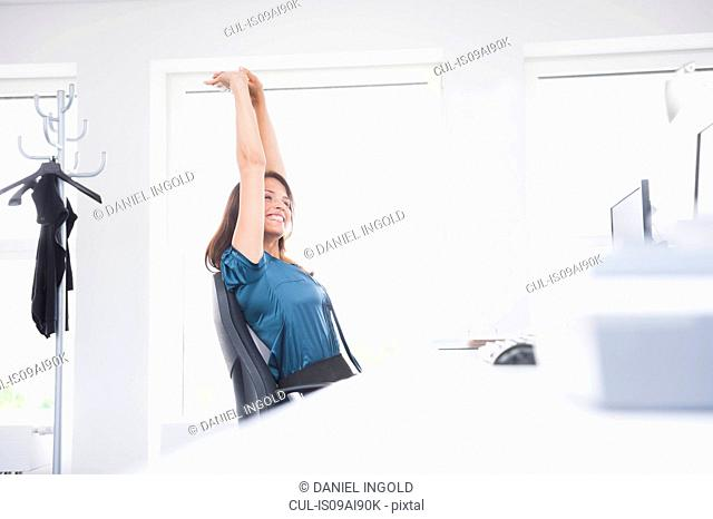 Woman with arms raised at desk