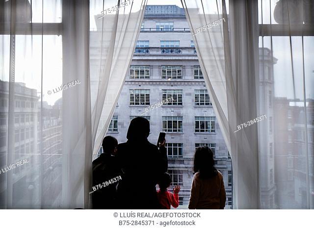Silueta de una mujer y dos adolescentes irreconocibles haciendo una foto con un telefono movil a traves de una ventana a un edificio