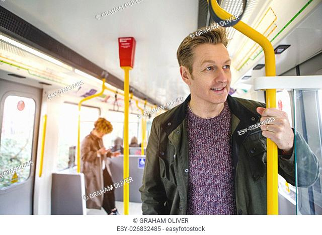 Man standing on the train holding on to the hand rail. He is looking out the window with a cheerful expression