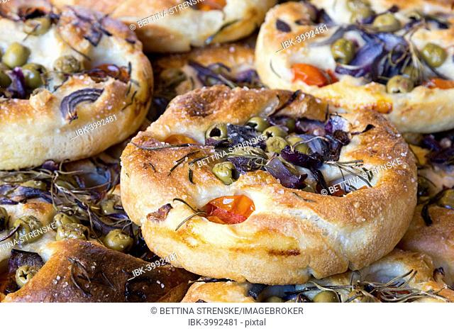 Focaccia, Italian flat bread made from yeast yeast dough with herbs, tomatoes and olives