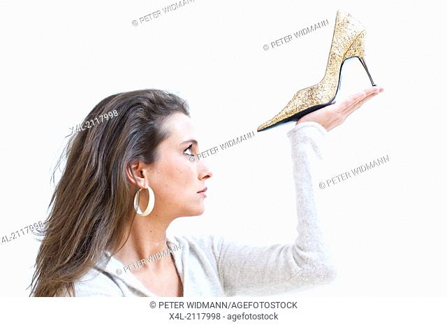 Young woman admiring a golden high heeled shoe (model-released)