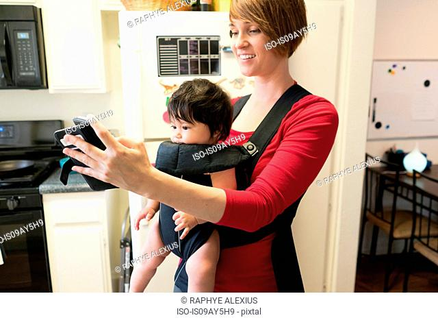 Mother with baby in carrier, using mobile phone