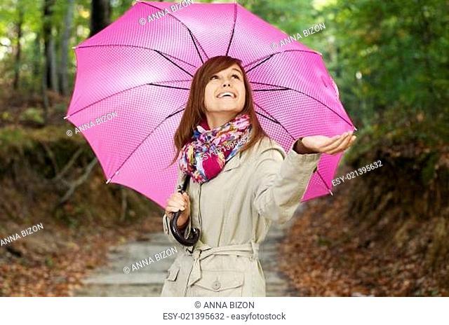 Beautiful girl with umbrella checking for rain