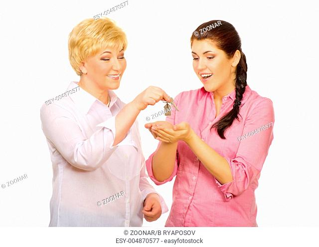 Senior woman give keys to young woman isolated